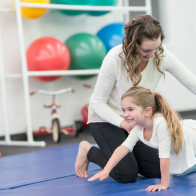 Cute young girl does recovery exercises with her physical therapist at a clinic. She is doing a balancing exercise on the mat and has a big smile. There is a rack of medicine balls and play equipment in the. background, including a pair of tricycles.